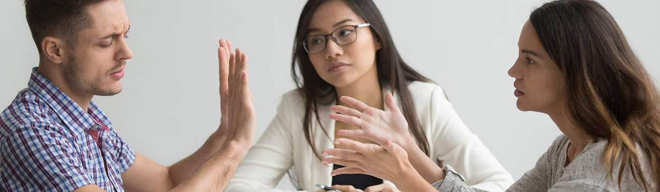 A husband and wife sit at a table and discuss their divorce with a young female mediator in VA